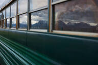 Reflection of mountain ranges on windows of mobile home bus, Homer, Alaska, United States - ISF21671