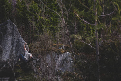 Climber bouldering in forest, Squamish, Canada - ISF21713