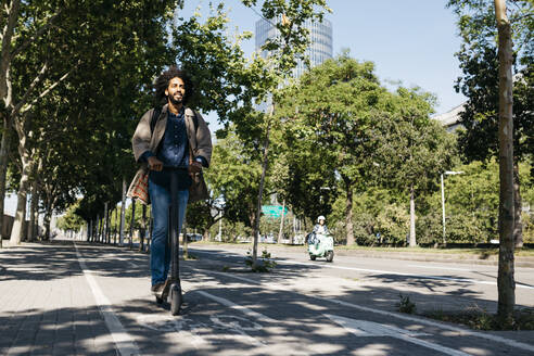 Spain, Barcelona. Young afro man going to work with his electric scooter by a bicycle lane - JRFF03343