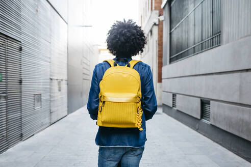 Back view of young man with yellow backpack on E-Scooter in the city - JRFF03361