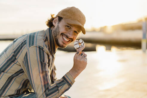 Portrait of laughing man eating doughnut at sunset - AFVF03342