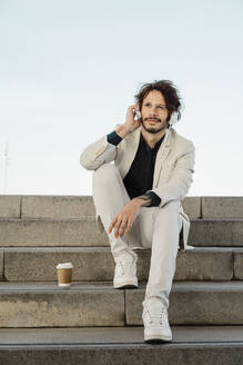 Portrait of businessman with coffee to go sitting on staris outdoors listening music with headphones - AFVF03366