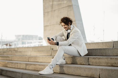 Smiling businessman with headphones sitting on stairs outdoors looking at cell phone - AFVF03369