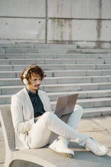 Businessman with headphones working on laptop outdoors - AFVF03378