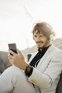 Portrait of smiling businessman with headphones and laptop looking at his mobile phone - AFVF03381
