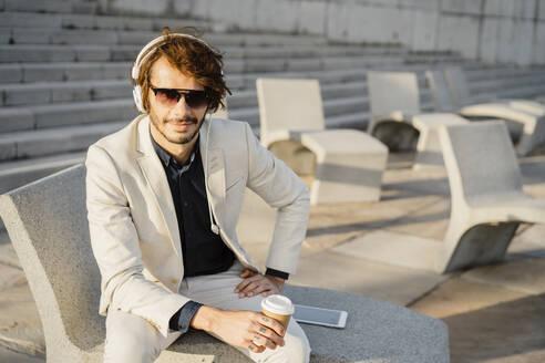 Portrait of businessman wearing sunglasses listening music with headphones - AFVF03390