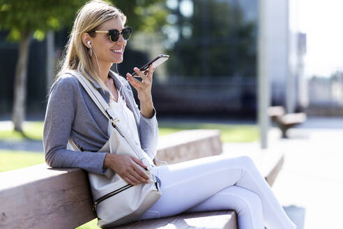 Young businesswoman talking on the smartphone with hands free while sitting on bank - JSRF00291