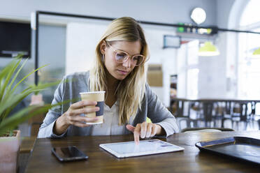 Young woman working with her digital tablet while drinking coffee in the coffee shop - JSRF00294
