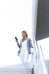 Young businesswoman listening to music with mobile phone on stairs - JSRF00303