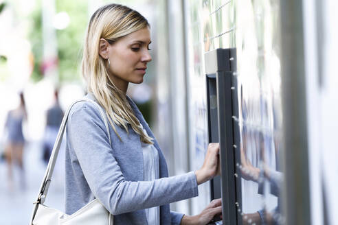 Young businesswoman using a credit card to withdraw money on a cash machine outdoors - JSRF00306