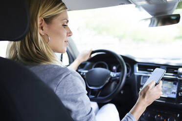 Young woman using her mobile phone in the car - JSRF00309