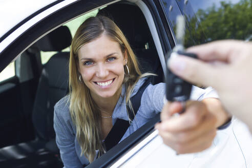 Portrait of smiling young woman looking at camera while holding car keys and give it to someone through the window - JSRF00312