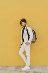 Portrait of businessman with backpack leaning at yellow wall - AFVF03410