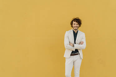 Portrait of smiling businessman in front of yellow wall - AFVF03413
