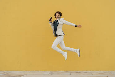 Happy businessman jumping in the air in front of yellow wall listening music with headphones - AFVF03416