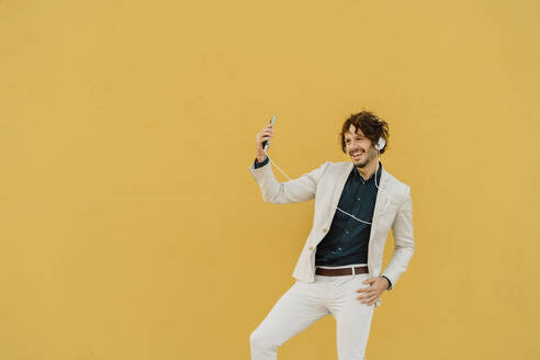 Businessman dancing in front of yellow wall listening music with headphones and smartphone - AFVF03419