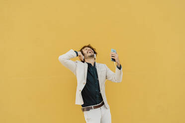 Businessman singing and dancing in front of yellow wall listening music with headphones and smartphone - AFVF03422