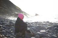 Girl in deep thought on rocks by sea - CUF51486