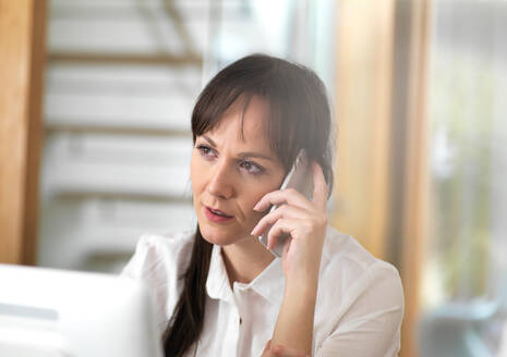 Woman talking through a business issue over the phone - CUF51525