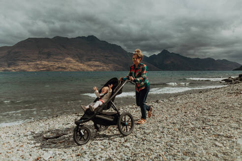 Mother with baby in pram walking on beach, Queenstown, Canterbury, New Zealand - ISF21820