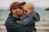 Father kissing baby on beach - ISF21823
