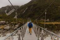 Hiker crossing suspension bridge, Wanaka, Taranaki, New Zealand - ISF21856