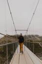 Hiker crossing suspension bridge, Wanaka, Taranaki, New Zealand - ISF21865