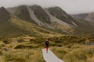Woman jogging on trail path, Wanaka, Taranaki, New Zealand - ISF21871