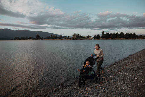 Mother with baby in pram walking on beach, Te Anau, Southland, New Zealand - ISF21880