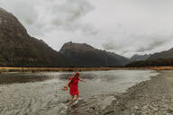 Woman exploring lake, Queenstown, Canterbury, New Zealand - ISF21886