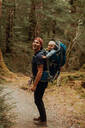 Hiker with baby exploring forest, Queenstown, Canterbury, New Zealand - ISF21895