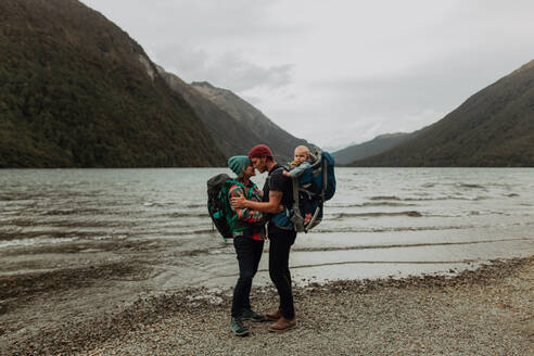 Parents with baby kissing on beach, Queenstown, Canterbury, New Zealand - ISF21898