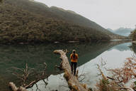 Woman enjoying scenic lake view, Queenstown, Canterbury, New Zealand - ISF21907