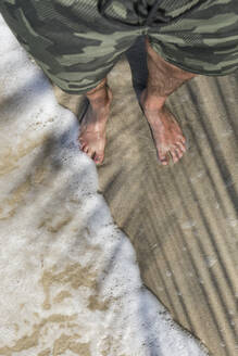 Feet of a man standing on a sandy beach enjoying the waves, Cahuita National Park, Costa Rica - MAUF02607