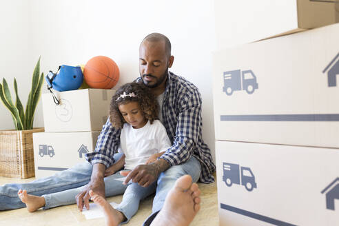 Father and daughter sitting on the floor at new home surrounded by cardboard boxes - JPTF00176