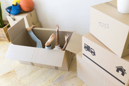 Unrecognisable girl inside cardboard box at new home - JPTF00179
