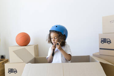 Girl inside cardboard box at new home closing bicycle helmet - JPTF00182