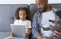 Father and excited daughter sitting on couch at home looking at tablet - JPTF00185