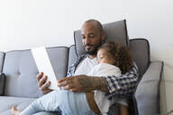 Father and daughter sitting on couch at home together looking at tablet - JPTF00188