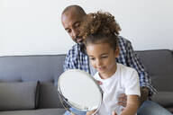 Father with daughter looking in mirror on couch at home - JPTF00194