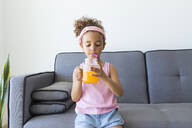 Girl sitting on couch at home having a drink - JPTF00200