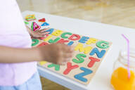 Close-up of girl playing with alphabet learning game on table - JPTF00203