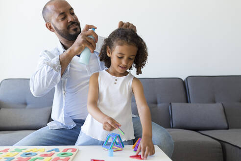 Father doing daughter's hair on couch at home - JPTF00206