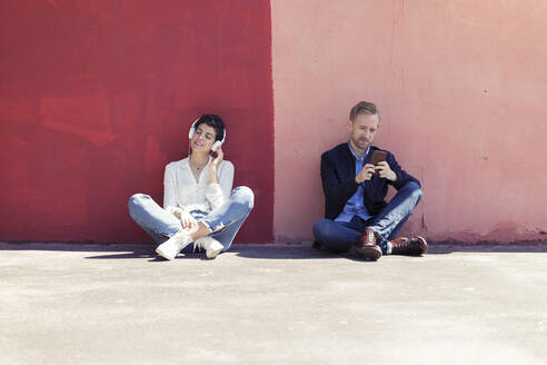 Couple leaning on a wall, man using smartphone, woman with white headphones - JSRF00314