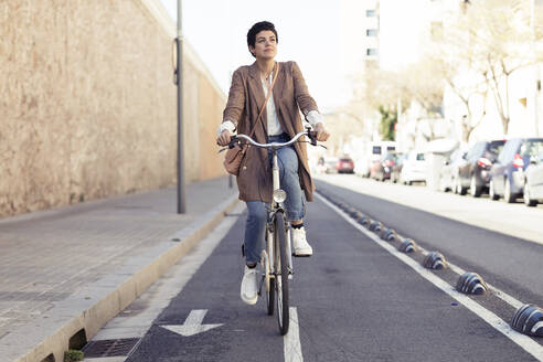 Woman with bike on bicycle lane in the city - JSRF00353