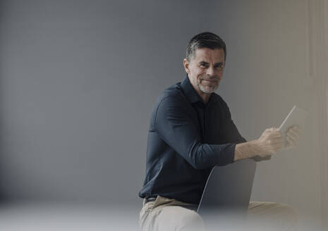 Smiling mature businessman sitting on chair using tablet - KNSF06047