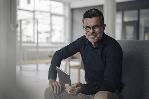 Portrait of confident mature businessman with tablet - KNSF06062