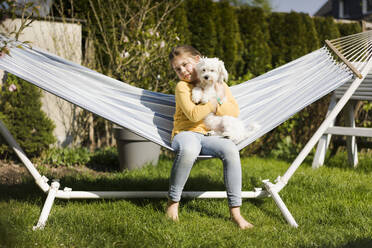 Portrait of girl with dog in hammock in garden - MOEF02270