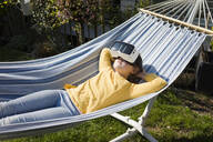 Girl lying in hammock in garden wearing VR glasses - MOEF02273