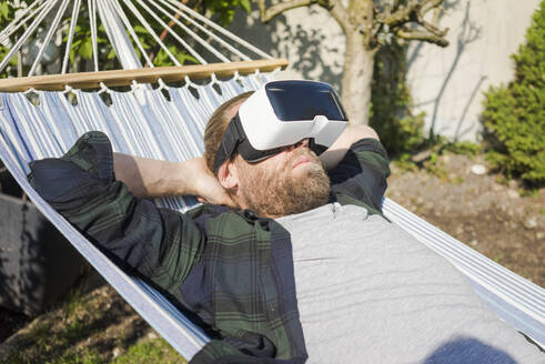 Man lying in hammock in garden wearing VR glasses - MOEF02276